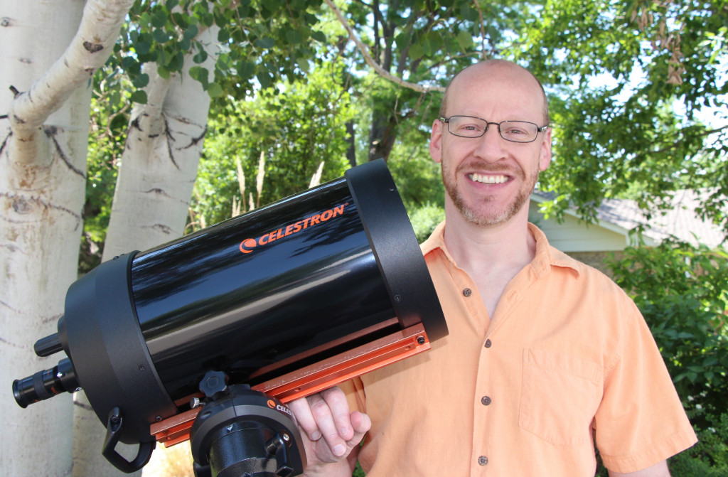 Phil Plait holding a telescope.